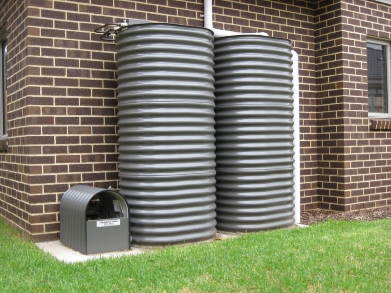 two rain water tanks, grey, against a brick wall